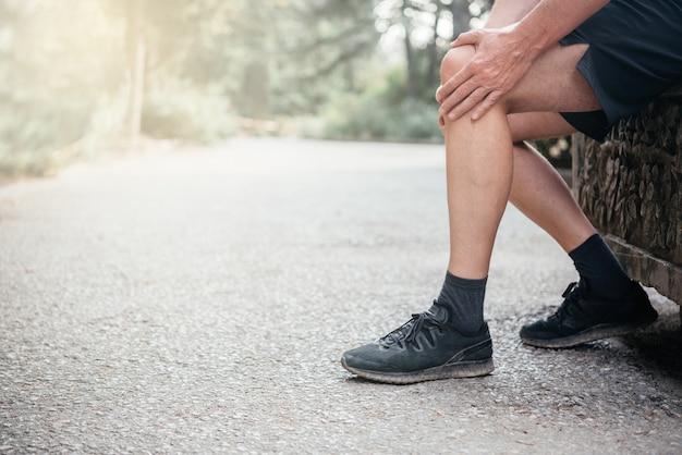 Uomo anziano che ha dolore al ginocchio durante l'esercizio di lesioni sportive concept