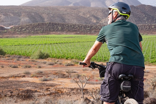 Uomo anziano sulla sua bicicletta elettrica in escursione all'aperto sotto il sole indossando casco sportivo e occhiali da sole. vigna verde e montagna sullo sfondo