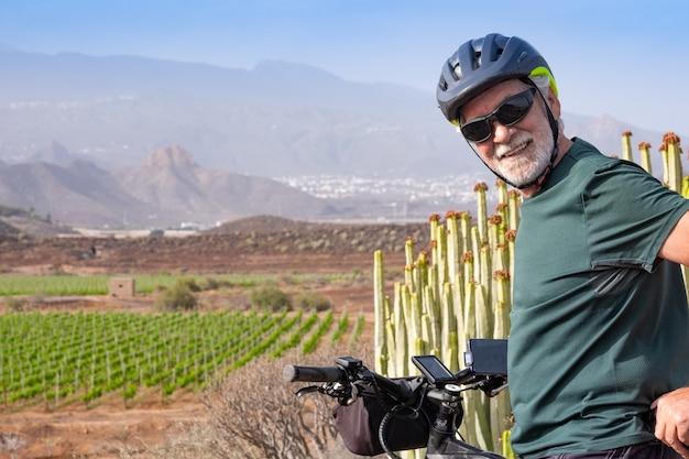 Uomo anziano sulla sua bici elettrica all'aperto. vigna verde e montagna sullo sfondo