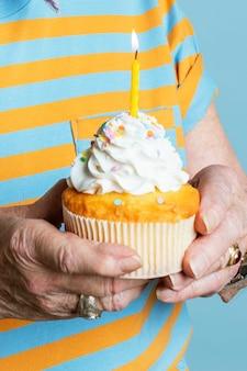 Uomo anziano con in mano un cupcake di compleanno