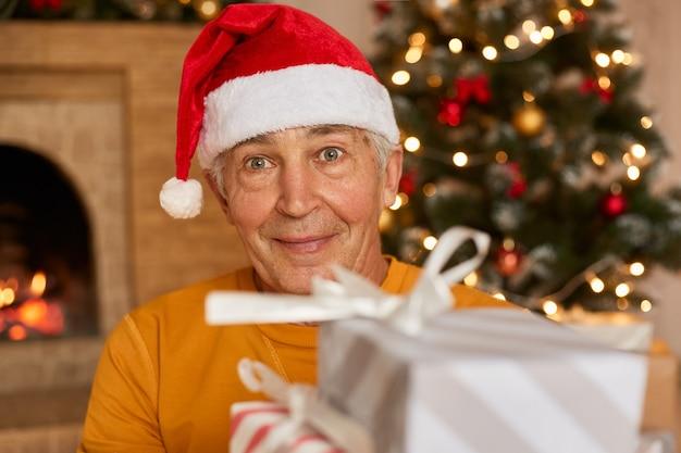 Uomo anziano che tiene scatola regalo con camino e albero di natale, con grandi occhi, maschio indossa camicia gialla e cappello rosso festivo.