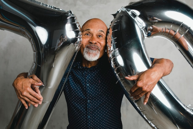 Uomo anziano che tiene palloncini d'argento per la celebrazione di 10 anni