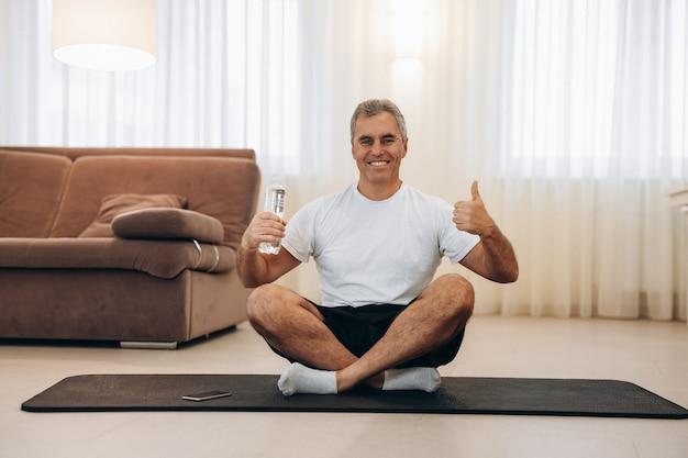 Uomo anziano che tiene in mano una bottiglia d'acqua, alza il pollice e si siede con le gambe incrociate crossing