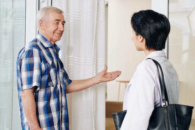 Uomo maggiore che invita il rappresentante della compagnia di assicurazione sanitaria