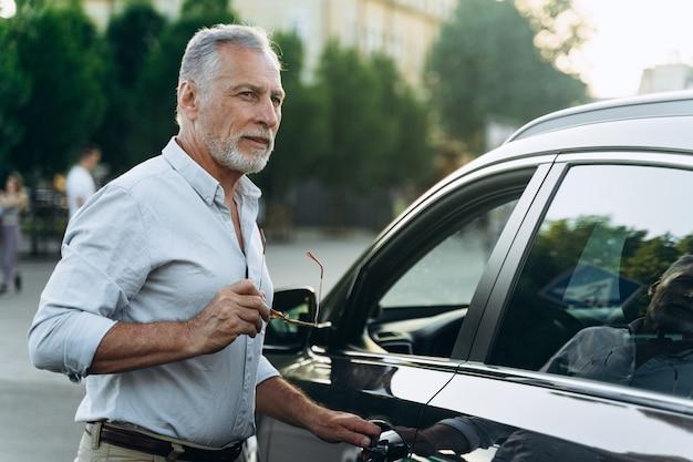 L'uomo anziano è in piedi vicino alla sua auto suv e tiene in mano gli occhiali da sole. ritratto di uomo di mezza età all'aperto vicino alla sua auto