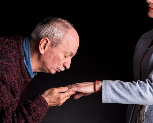 Uomo anziano che bacia la mano di una donna su uno sfondo scuro