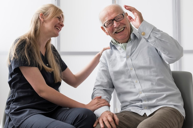 Uomo maggiore che ride con l'infermiera in una casa di cura