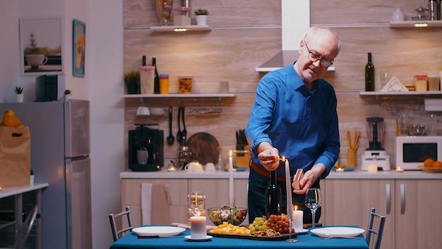 Uomo anziano che accende la candela in attesa di sua moglie per una cena romantica. vecchio marito anziano che prepara un pasto festivo con cibo salutare per la celebrazione dell'anniversario, seduto vicino al tavolo in cucina.