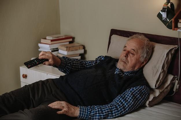Uomo anziano che fa un pisolino mentre è sdraiato a letto e guarda la tv con un telecomando, riposando in un letto