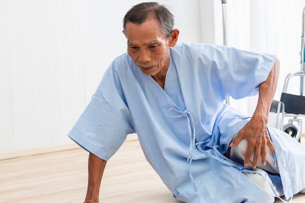 Incidente paziente dell'uomo senior che cade e che striscia per l'aiuto nella stanza di ospedale.