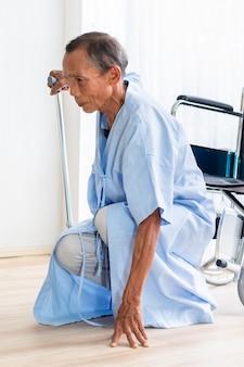 Strisciare paziente dell'uomo senior per aiuto nella stanza di ospedale