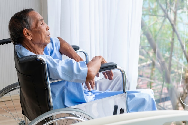 Paziente dell'uomo senior in sua sedia a rotelle in ospedale