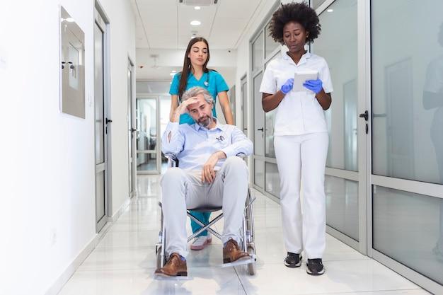 Paziente uomo anziano in sedia a rotelle seduto nel corridoio dell'ospedale con medico e infermiere
