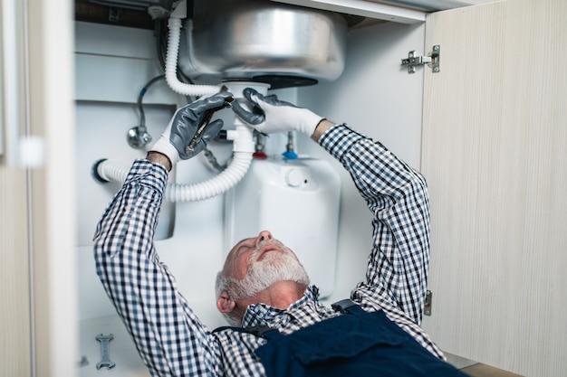Idraulico uomo anziano che lavora con strumenti idraulici in cucina. ristrutturazione.