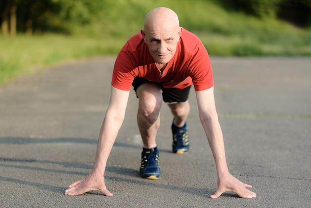 Uomo maggiore in posizione pronto per essere eseguito. uomo determinato pronto per uno sprint. stile di vita sano e concetto di avvio di esercizio