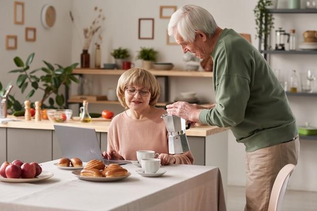 Uomo anziano che versa il tè caldo nella tazza di sua moglie mentre lavora online sul laptop al tavolo durante la colazione