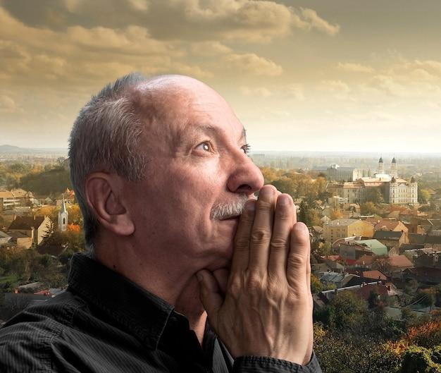 Uomo anziano che prega contro il paesaggio urbano
