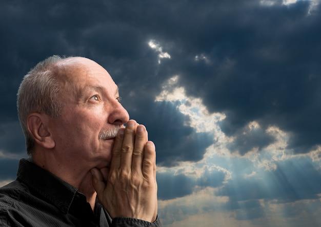 Uomo anziano che prega contro il cielo nuvoloso blu