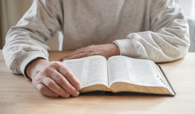 Uomo anziano che prega, leggendo una vecchia bibbia nelle sue mani.