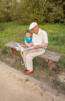 Uomo anziano che legge giornale e bambino carino che punta un articolo con il dito seduto su una panchina del parco. due diverse generazioni concetto.