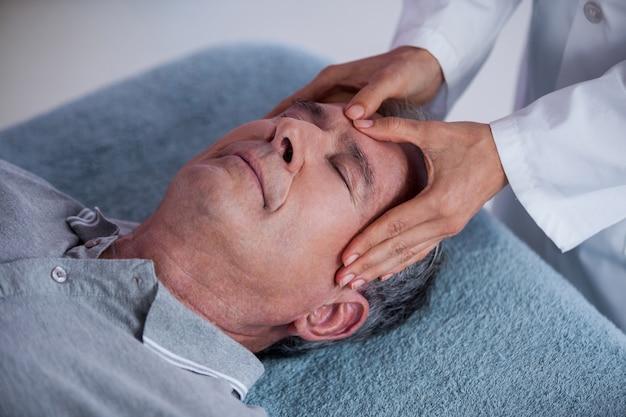 Uomo senior che riceve massaggio capo dal fisioterapista
