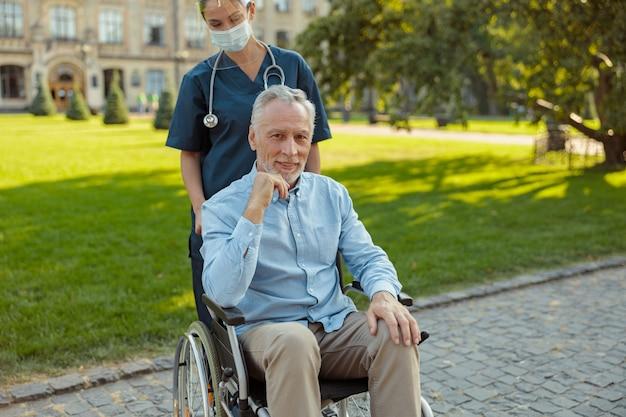 Uomo anziano che sta recuperando un paziente su una sedia a rotelle che guarda la telecamera durante una passeggiata con un'infermiera