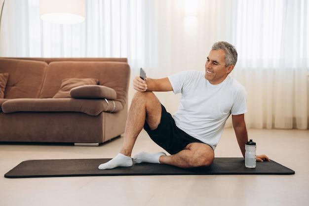 Uomo anziano che riposa dopo l'allenamento a casa con acqua e telefono