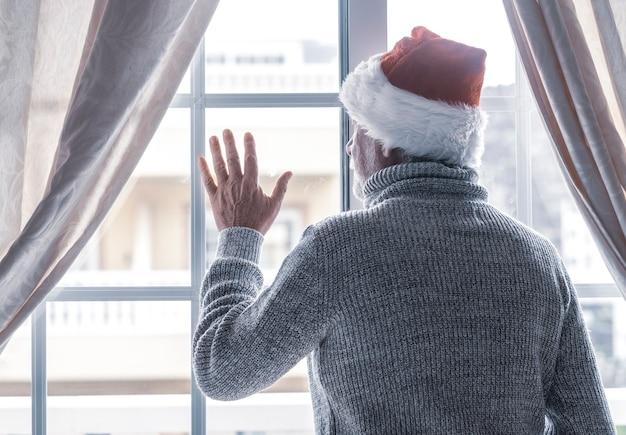 Un uomo anziano con un cappello da babbo natale e un maglione grigio rimane a casa dietro la finestra a guardare fuori