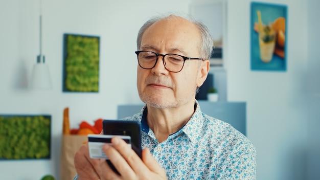 Uomo anziano che acquista online utilizzando smartphone e tenendo la carta di credito durante la colazione in cucina. persona anziana in pensione che utilizza la banca domestica di pagamento tramite internet che acquista con la tecnologia moderna
