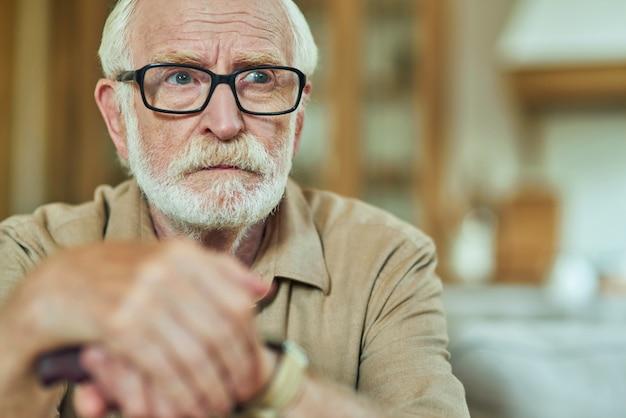 Uomo anziano seduto e con in mano un bastone da passeggio in legno a casa