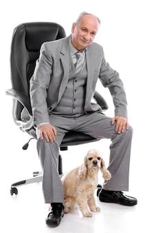 Senior uomo seduto sulla sedia da ufficio con american cocker spaniel isolato