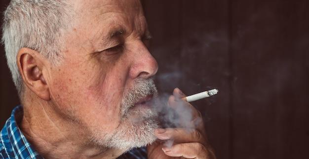 Sigaretta di fumo dell'uomo maggiore fuori, cattiva abitudine