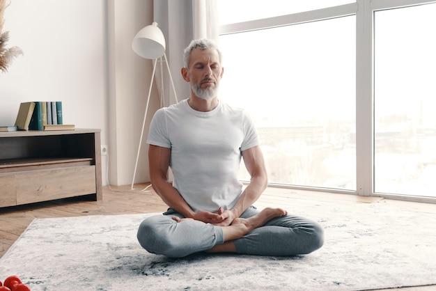 Uomo anziano in abbigliamento sportivo che medita mentre è seduto sul pavimento nella posizione del loto a casa