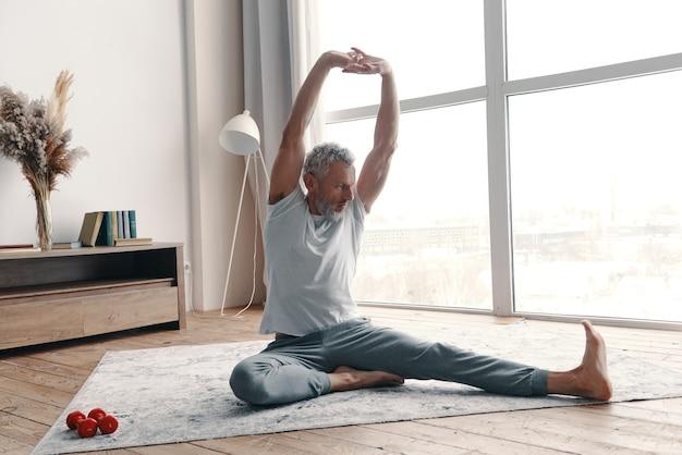 Uomo anziano in abbigliamento sportivo che si allunga mentre è seduto sul pavimento vicino alla finestra di casa