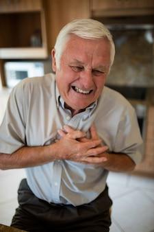 Uomo anziano che soffre di infarto in cucina a casa