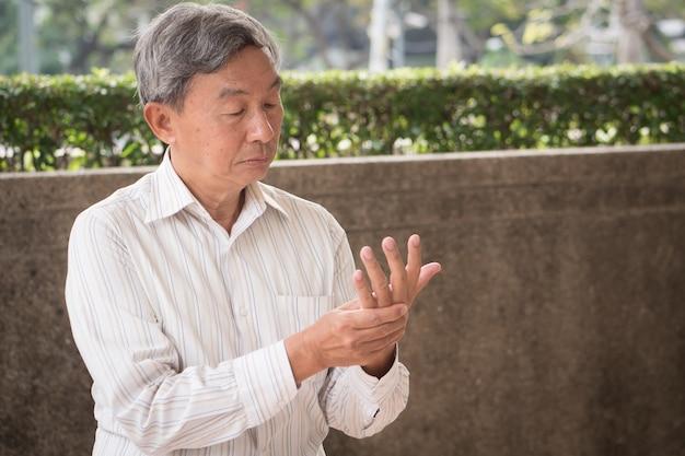 Uomo maggiore che soffre di dito a scatto