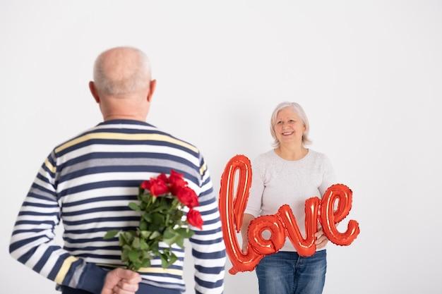 Moglie sorprendente dell'uomo anziano con le rose.