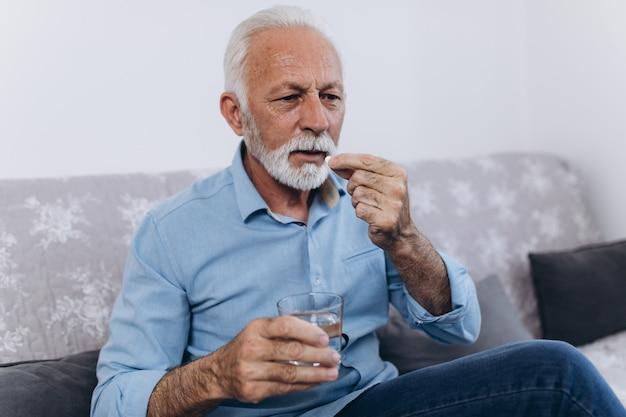 Uomo anziano che prende medicine a casa.
