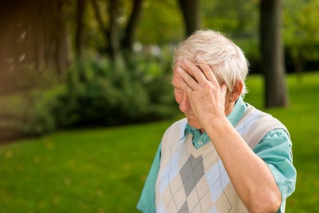 Uomo anziano che si tocca la fronte.