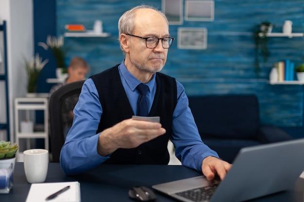 Uomo anziano che usa la carta di credito per controllare il conto bancario