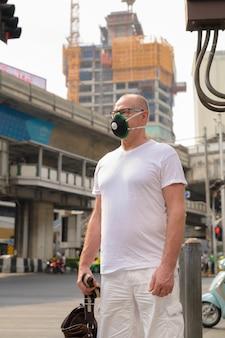 Uomo maggiore che utilizza la maschera per il viso per proteggere dallo smog di inquinamento in città