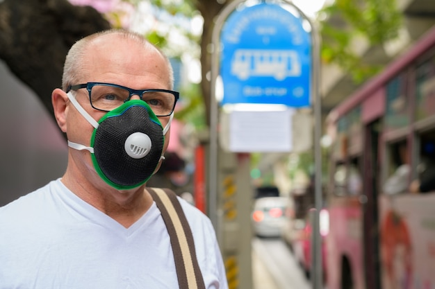 Senior uomo utilizzando la maschera per il viso per proteggere dallo smog di inquinamento
