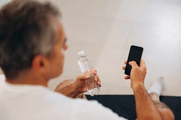 Uomo anziano che usa il suo smartphone e tiene in mano una bottiglia d'acqua di plastica