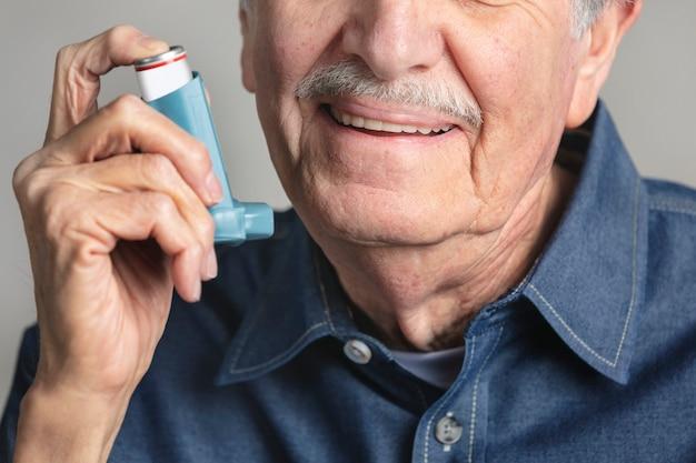 Uomo anziano che usa un inalatore
