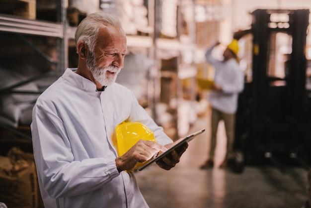 Uomo senior che utilizza compressa nel magazzino.