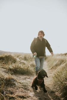 Uomo anziano che porta a spasso il suo cane su un sentiero costiero