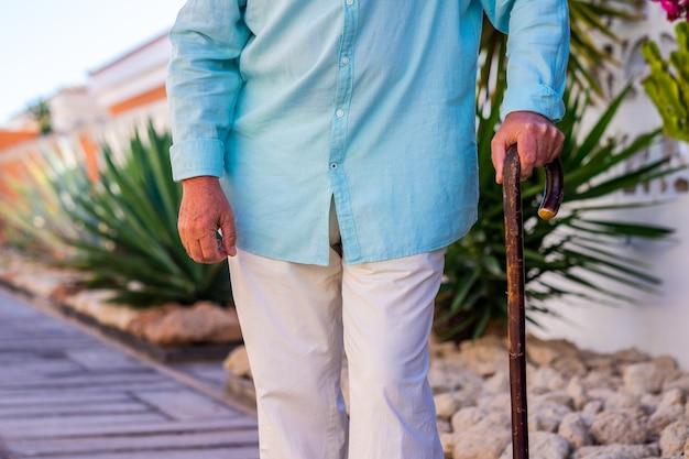 Uomo anziano che cammina all'aperto con l'aiuto di un bastone di legno. giardino sullo sfondo