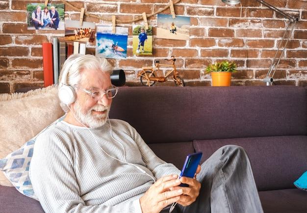 Uomo anziano che indossa le cuffie seduto sul divano e usa il telefono cellulare a casa - concetto di pensione, tempo libero e persone