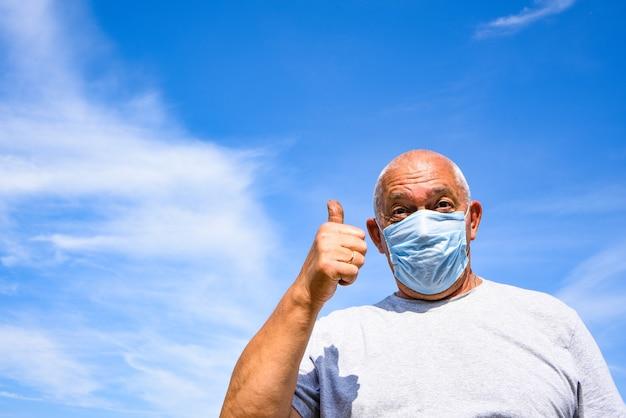 Uomo anziano che indossa maschera medica e occhiali di protezione guardando la telecamera e mostra i pollici in su.