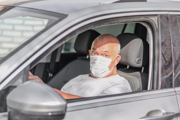 Senior uomo che indossa una maschera medica mentre si guida un'auto